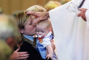 The widow of a September 11 attack victim kisses her daughter as a priest blesses her during her husband's funeral in Princeton, New Jersey. Photo by David Gard/ The Times of Trenton