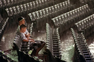 Julian Faria, 11, and Nicholas Faria , 15, Faria calmly accept the rain delay in a Trenton Thunder baseball game. Photo by David Gard/ The Times of Trenton