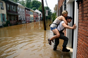 Eric Decibus carries his wife Pam to look at their Swan St. home in Lambertville, NJ. The first floor had 3 inches of water in it. Photo by David Gard/ The Times of Trenton