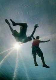 2 boys jump on a trampoline under a blazing sun. Photo by David Gard/The SandPaper