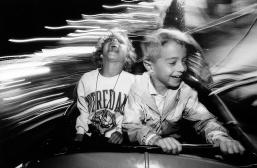 2 children enjoy a carnival ride. Photo by David Gard/Times Beacon Newspapers