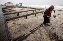 Steven Bernatowicz, 52, of Toms River hunts for treasure under a section of the boardwalk that was removed for renovation as Hurricane Sandy approaches Seaside Heights on Sunday evening, October 28, 2012. Photo by David Gard/The Star-Ledger