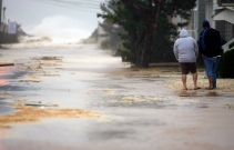 Residents Denise McCann, 48, and her husband Jim, 52, watch as Hurricane Sandy pushes the surf over the dunes and onto Harding Ave at high tide in Ortley Beach on Monday, October 29, 2012. Photo by David Gard/The Star-Ledger