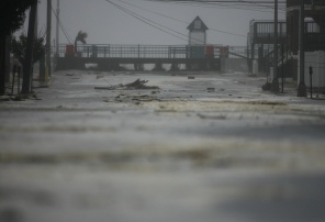 Ocean waves pass under the boardwalk and empty into the town as Hurricane Sandy strikes Seaside Heights on Monday evening, October 29, 2012. (Photo by David Gard/The Star-Ledger)