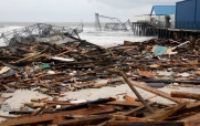 Debris litters the beach Seaside Heights on the day after Hurricane Sandy landed. Casino Pier and the Jet Star roller coaster are seen in the background. Tuesday, October 30, 2012. (Photo by David Gard/The Star-Ledger)