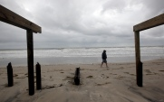 Joe Lanning, 49, walks near what is left of the northern part of the Seaside Heights boardwalk on the day after Hurricane Sandy landed. Tuesday, October 30, 2012. (Photo by David Gard/The Star-Ledger)