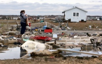 Lisa Kwabis returned to her Bayville home yesterday to find it had been ripped from the foundation and washed 200 feet away, landing half on land, half in a lagoon. A neighbor's relative looks over the debris field. The foundation is in the foreground, the house is in the distance.Thursday, November 01, 2012. (Photo by David Gard/The Star-Ledger)