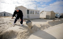 Ken Greulich uses a snow shovel to remove sand from the yard of his summer home in the Midway Beach section of South Seaside Park. Residents of South Seaside Park and Seaside Park where allowed back onto the Island today to retrieve items, clean-up and winterize homes ahead of the Nor'Easter. Monday, November 05, 2012. (Photo by David Gard/The Star-Ledger)